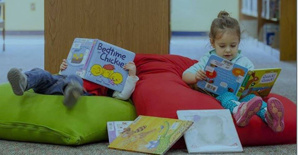 Two children read books on bean bag chairs