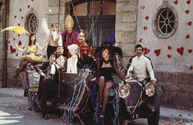 A group of people in costumes sit on a car