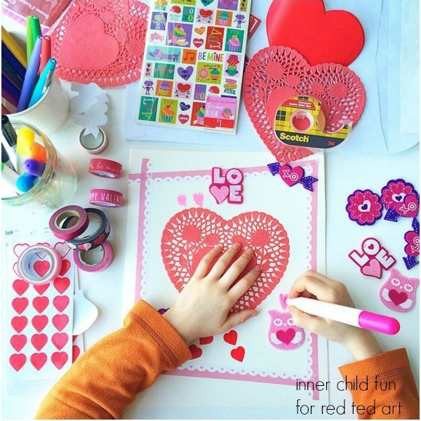 A pair of young hands makes a valentine's day card with crafting supplies
