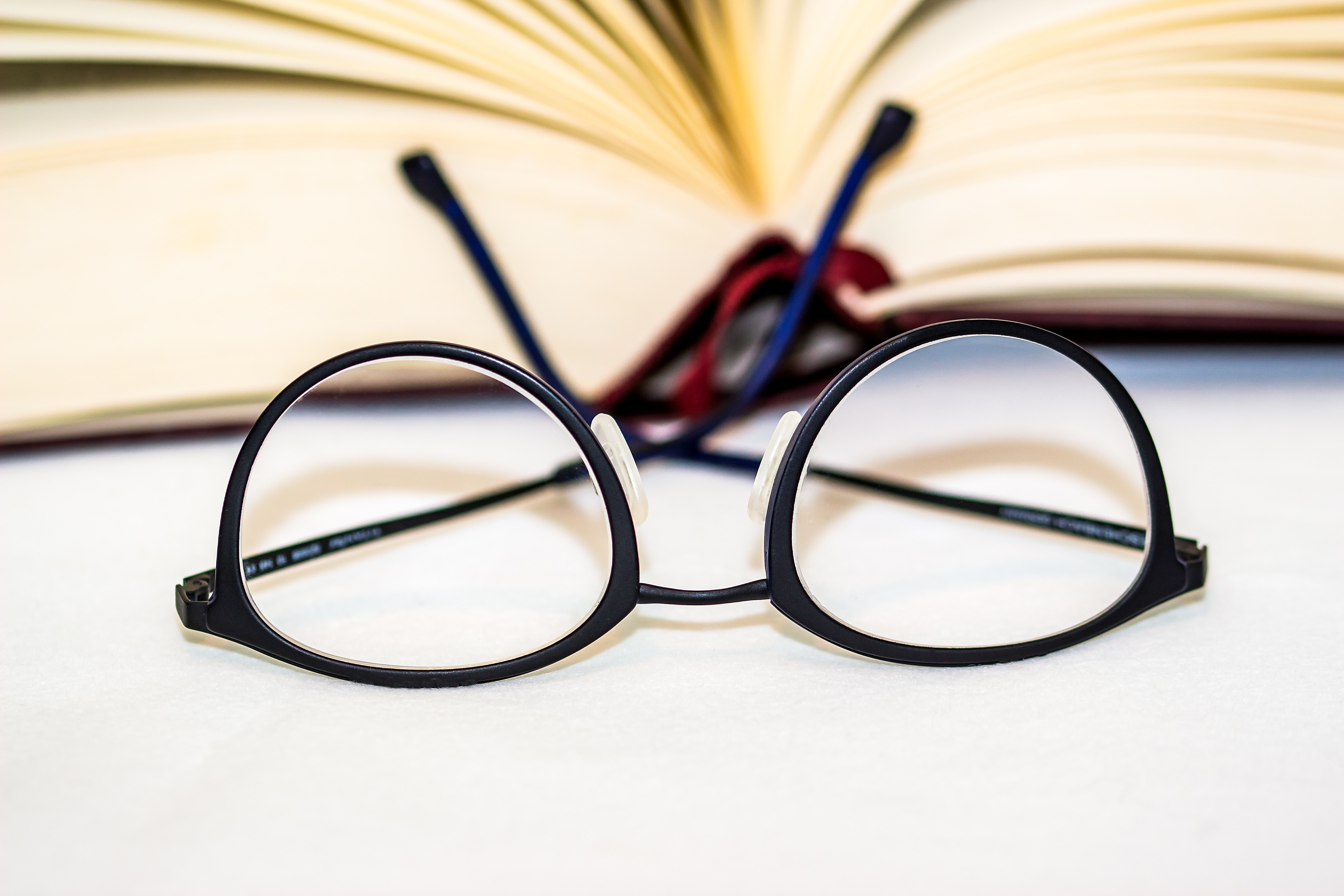 A pair of black glasses rests upside in front of a book