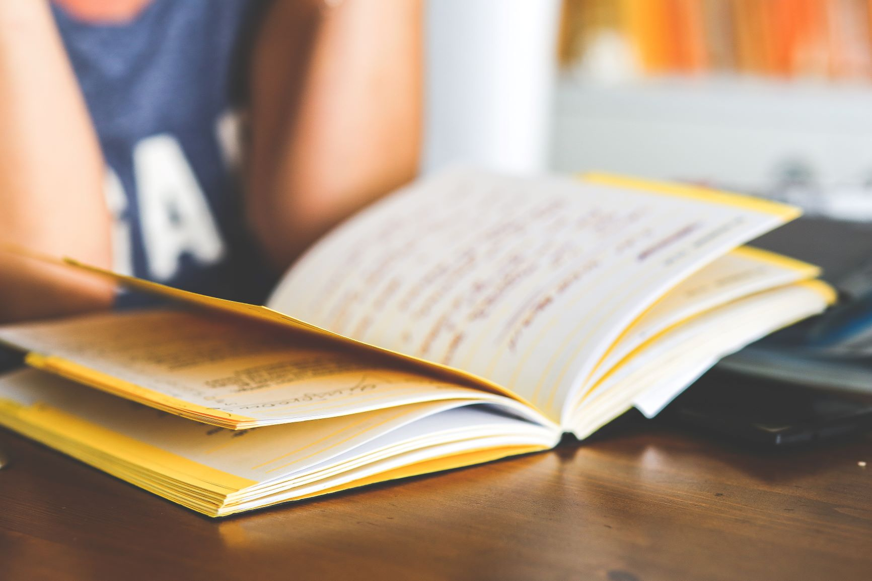 A woman reads from a yellow notebook