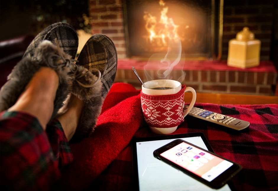 A pair of slippered feet reclines in front of a fire with a cup of steaming coffe and phone and remote next to it