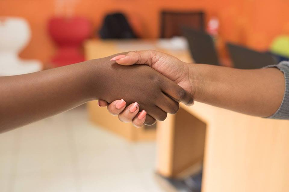 A pair of dark skinned hands shake