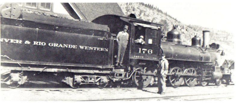Black and white image of men standing next to a train