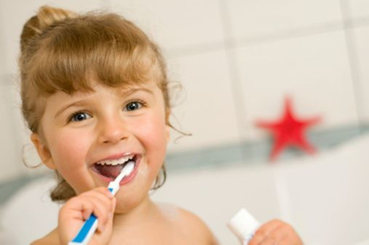 A young girl with blonde hair brushes her teeth with a blue and white toothbrush