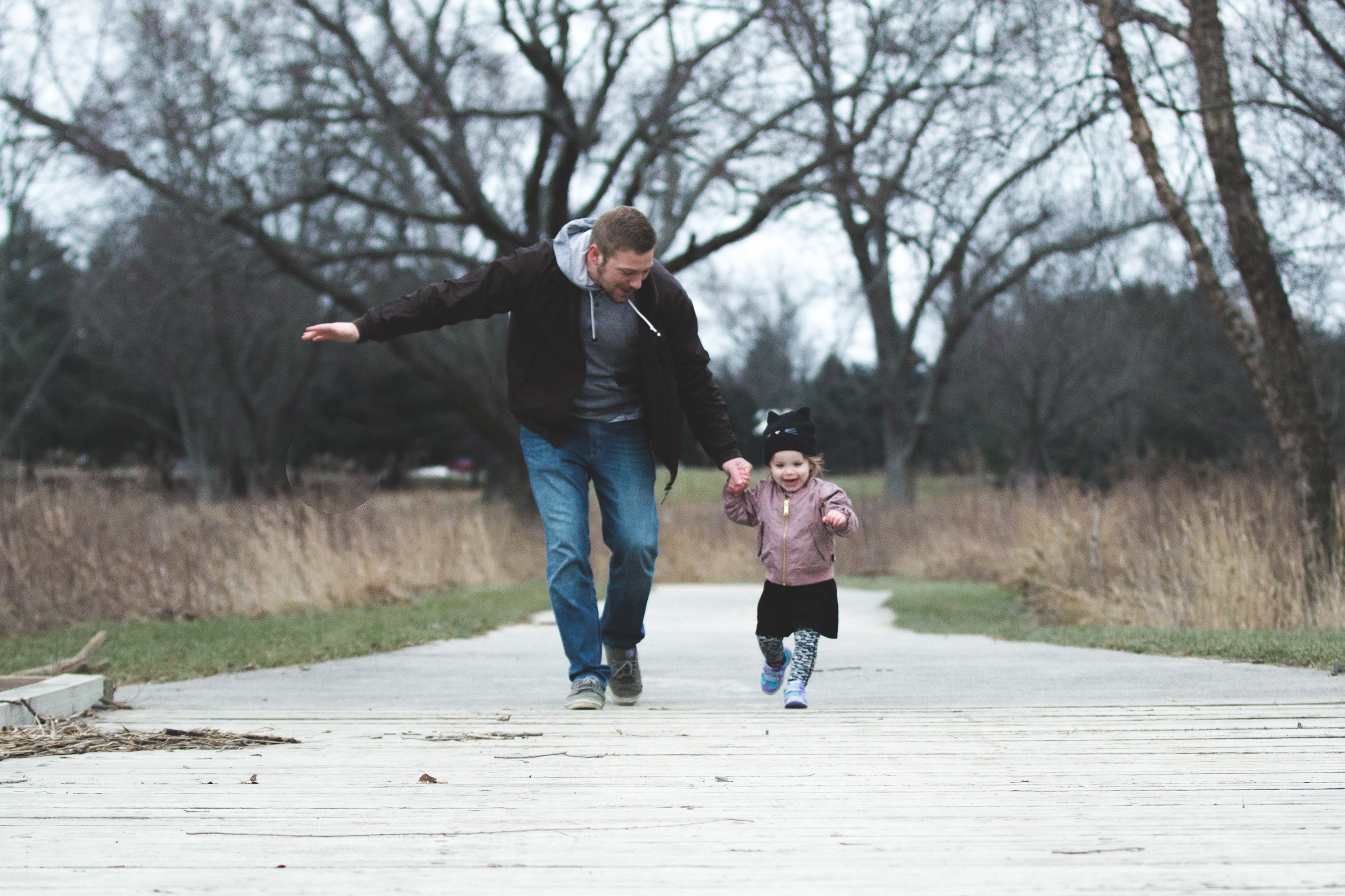 A man walks with a small female child down a pier