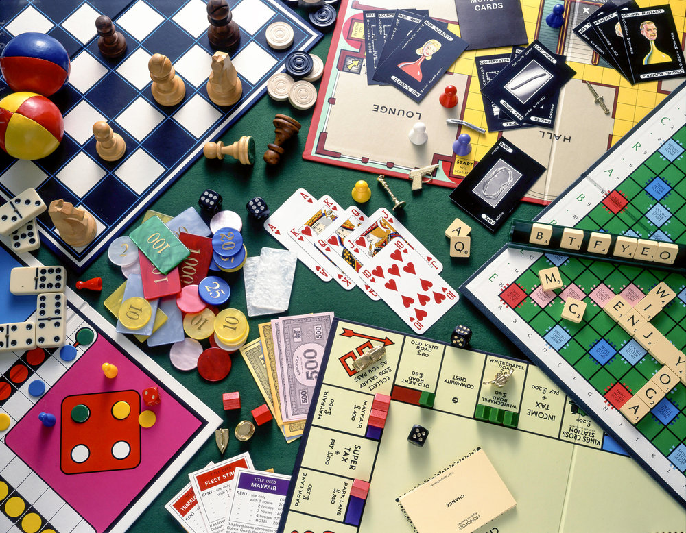 Still-life selection of board games (Monopoly, Chess, Cluedo, Scrabble) with playing cards and gambling chips