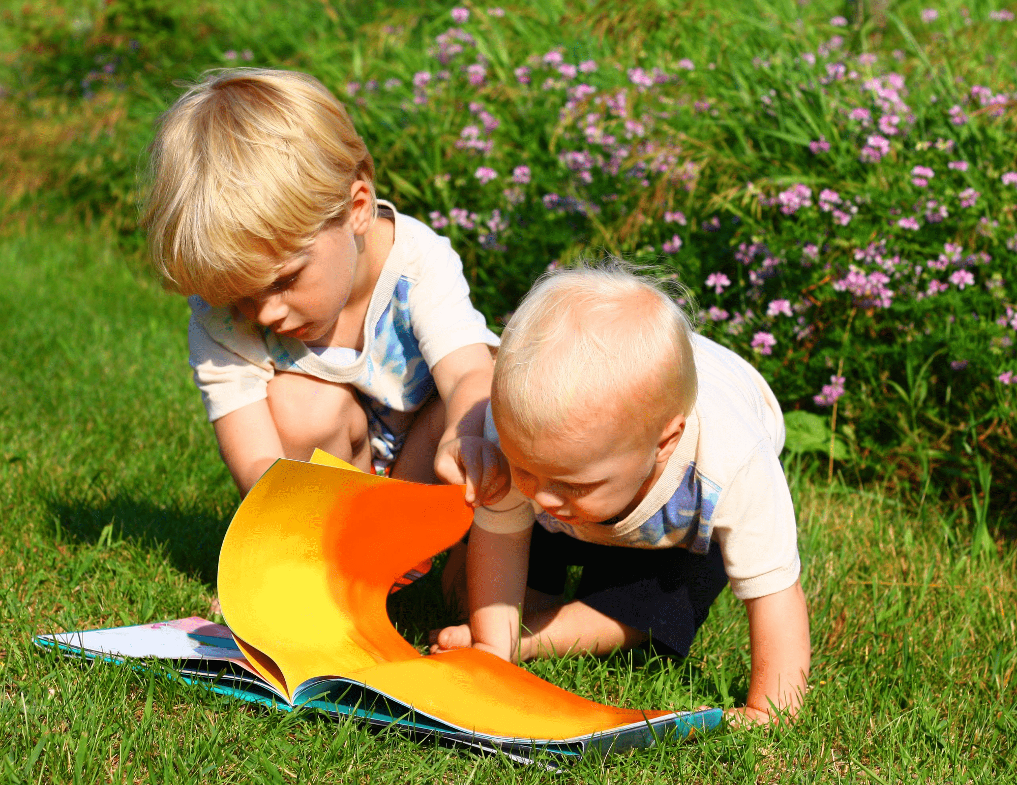 two children with blonde hair read a book outside